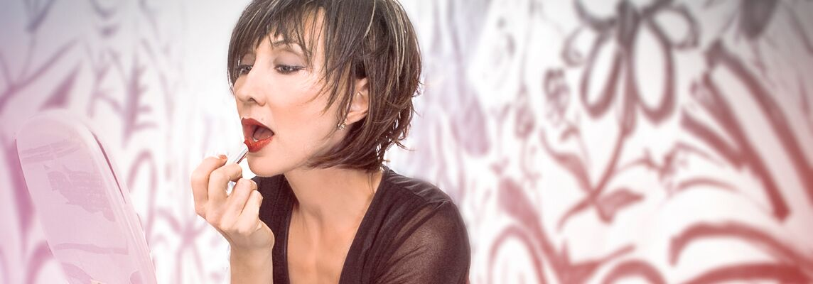 Pam Tillis putting on lipstick.