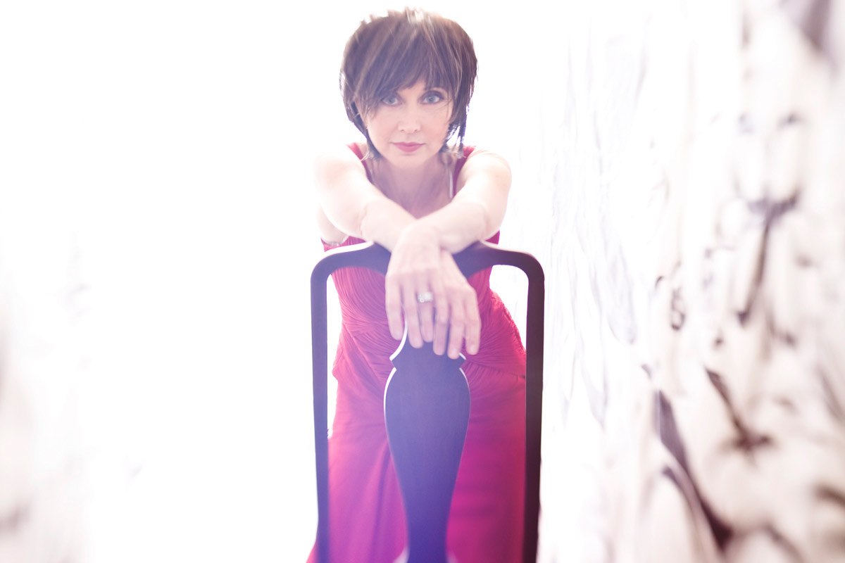 pam tillis red dress leaning on chair